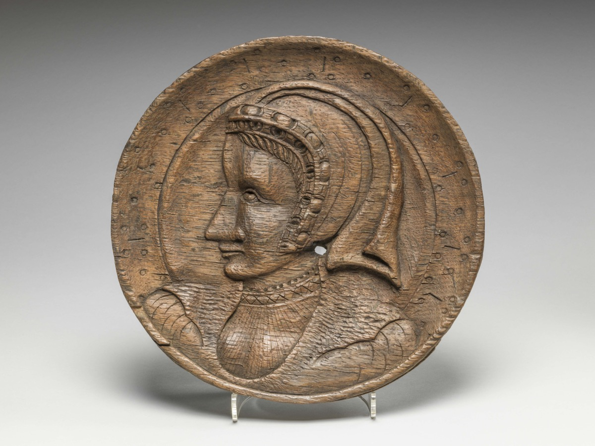 One of a pair of oak roundels, depicting the head of a woman in profile carved in low relief