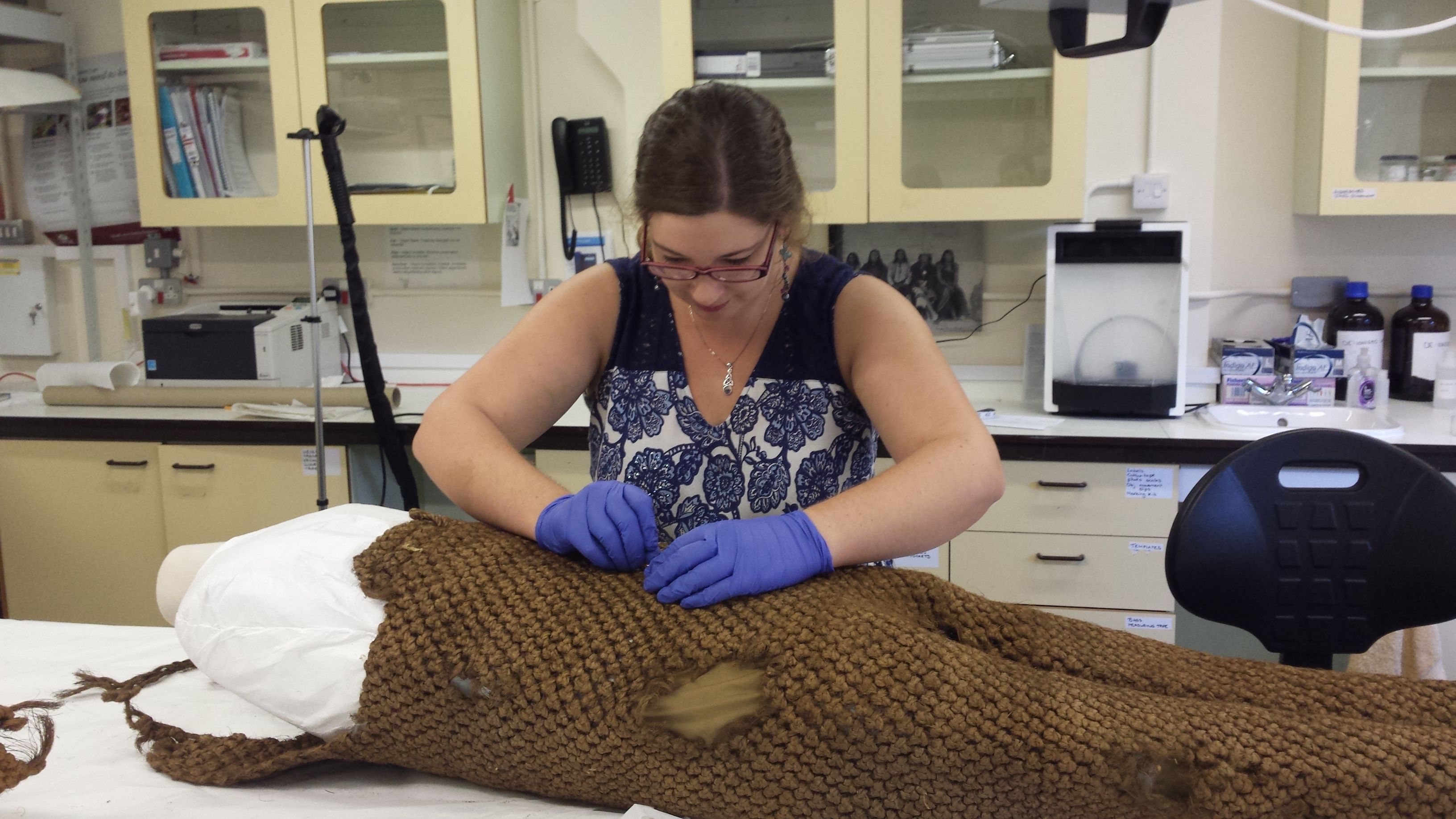 A museum conservator repairing woven overalls from Kiribati