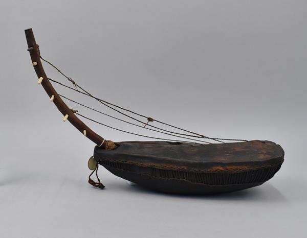 Dark brown musical instrument object, set against a grey studio background.