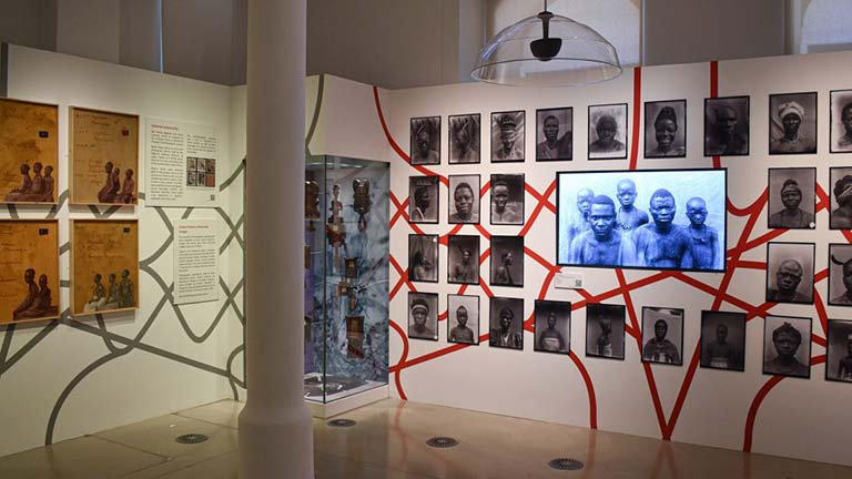 An exhibition shot of the Re Entanglements exhibition. On the right there is a display of headshots/photographs of people, with a video seen in the centre, intertwined by a graphic of red lines.