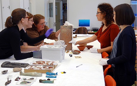 A lecturer and students examine objects in the Keyser workspace at MAA