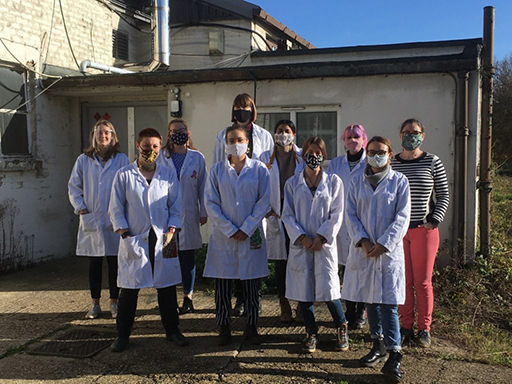 Nine women wearing face masks, eight wearing white lab coats, stand outside a building on a sunny day.