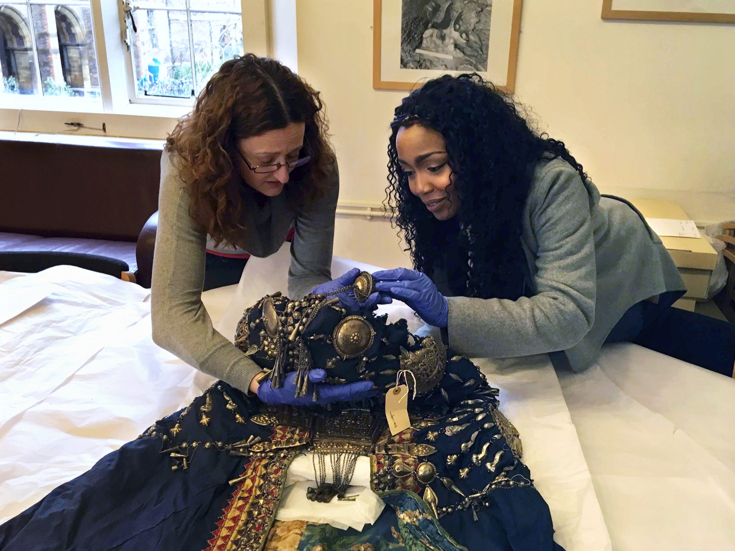 Researcher Vicky Ngari Wilson and Collections Manager for Anthropology Rachel Hand examining the robe of Abyssinian Queen Woyzaro Terunesh