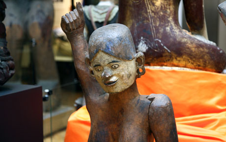 A wooden statue, life sized, of the wife of a chief of a village. Visible in the gallery with objects behind it.