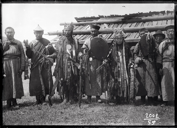 """A black and white photo of """"A shaman, a shamaness, and a Achinsk Lama with their helpers."""""""
