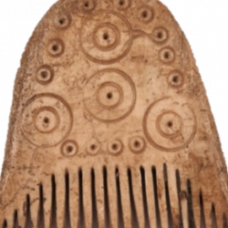 A rounded bone comb with narrow teeth. The body of the comb has circular detailing, smaller at the edge then four large circles interspersed throughout.