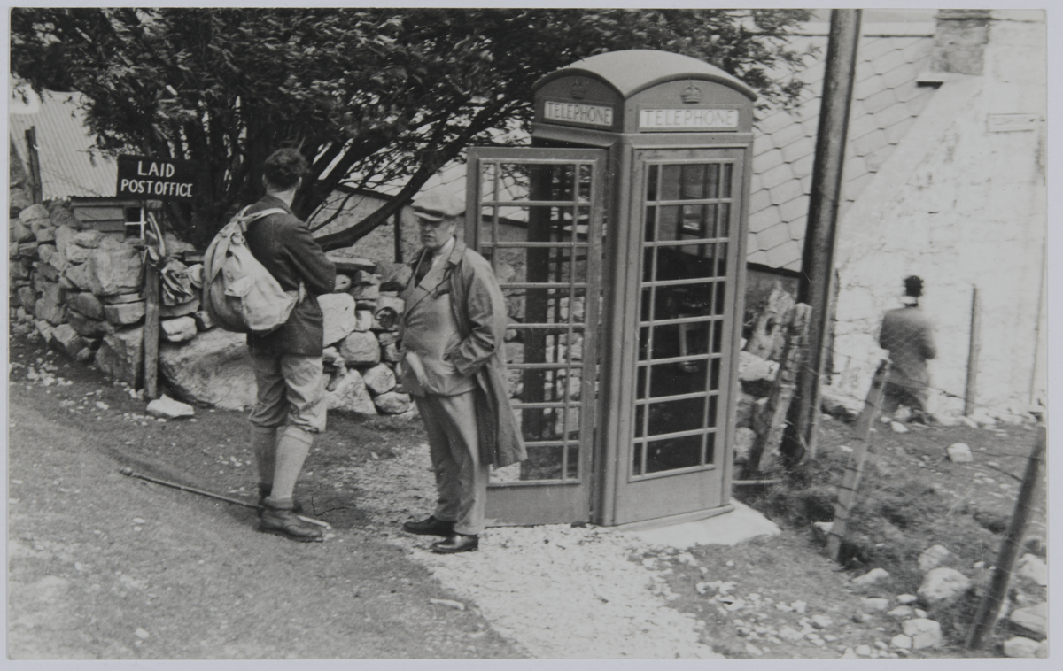 """Black and white photo of James Wordie and a second expedition member standing next a British telephone box and a sign pointing to """"Laid Post Office"""". Village buildings are in the background."""