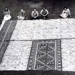 Museum workers seated around a piece of Fijian barkcloth, circa 1970-1980